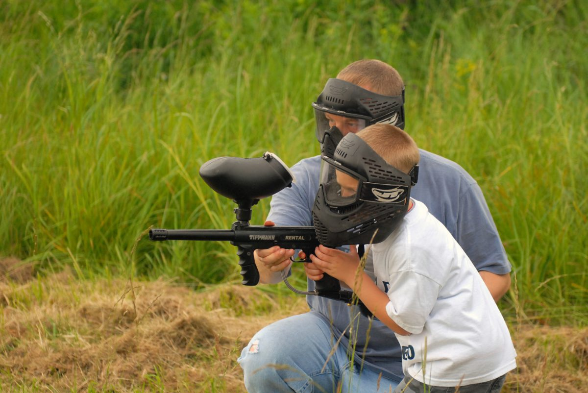 Spc. Melissa Church Sgt. 1st Class Allen Reome, master gunner in 3rd Squadron, 71st Cavalry Regiment, shows his son, Allen, how to shoot a paintball gun at a squadron father-son paintball competition June 19 on Fort Drum.